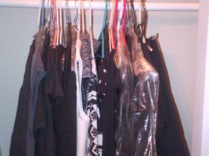 Black, grey and white dress hanging in a closet