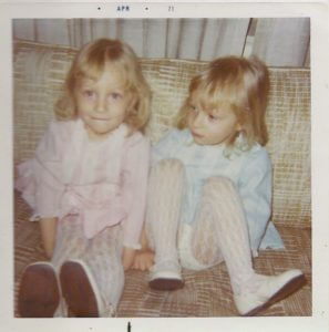 Identical twin sisters in pink and blue dress with lace tights and white patent leather shoes