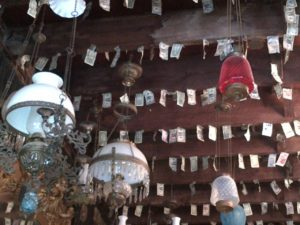 Lamps and dollar bills hanging from the ceiling of the French Quarter Chapel in New Orleans