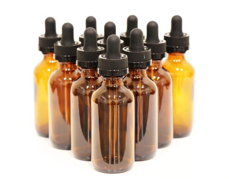 Ten amber bottles with black squeezable dropper caps to represent fragrance technology for an article about multi-sensorial products