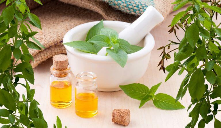 Two glass bottles of aromatherapy essential oils with cork stoppers with green herbs in a white mortar bowl with pestle for an ingredient article about herbalists formulating natural skincare products