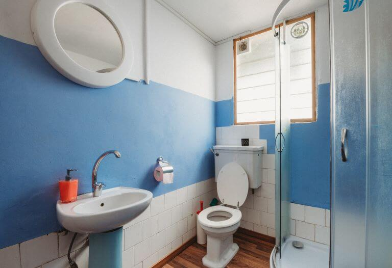 A blue and white bathroom with toilet, sink and shower for a fragrance article about air fresheners specifically formulated for toilets