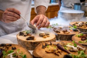 Chef preparing vegetables and mushroom on a wooden tree slab for an article about experiential dining