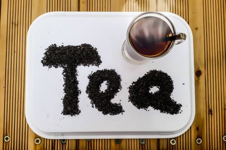 Cup of hot tea on a tray with tea leaves that spell out tea for an ingredient article about Earl Grey tea