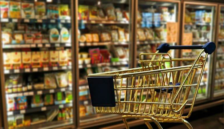 An empty gold grocery cart in front of a refrigerated section for a flavor trends article about new food and beverages