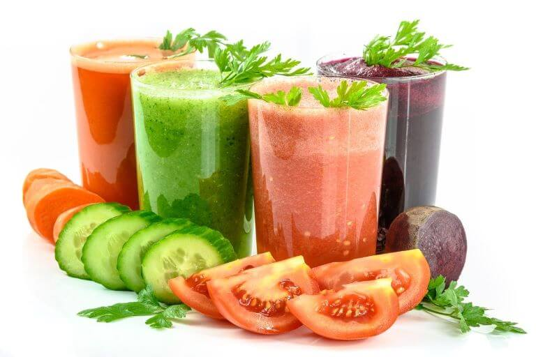 Fresh vegetable juices made from carrots, cucumber, tomato and beets for an article about functional ingestibles formulated for good health