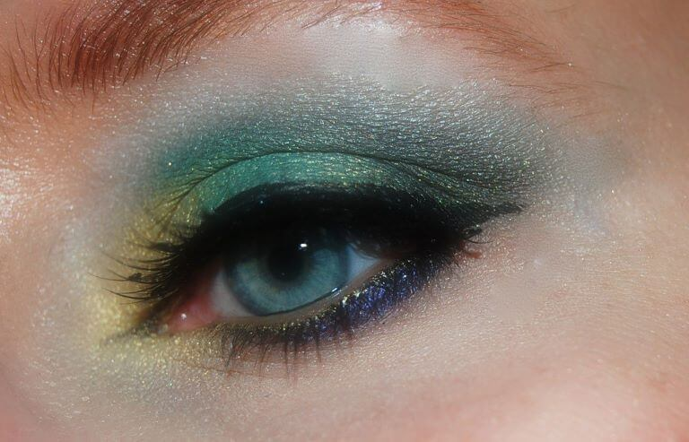A close up of a blue eye with rainbow colored glittery eye shadow for an article about scented products such as cosmetics