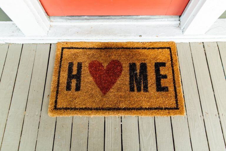 A door welcome mat with the word home on it for a lifestyle trend article about delivery and subscription-based products and services
