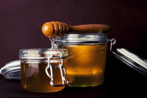 Two glass mason jars of honey with honey dipper on top for an ingredient article about new fragrance and flavor products