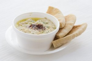 A white bowl of hummus and pita for an ingredient article about Middle Eastern flavors with a focus on chickpeas and hummus