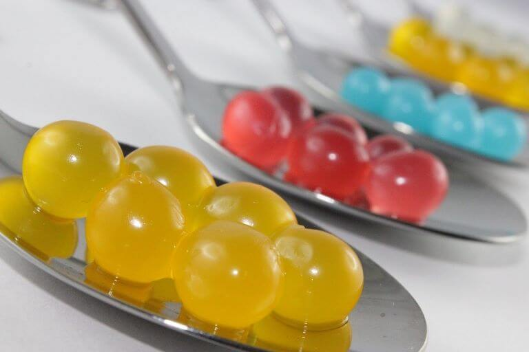 Close up of three silver spoons with edible yellow, red and blue beads for a multi-sensory article about molecular gastronomy