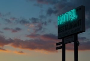 A turquoise neon hotel sign for an article about interactive themed hospitality and travel experiences