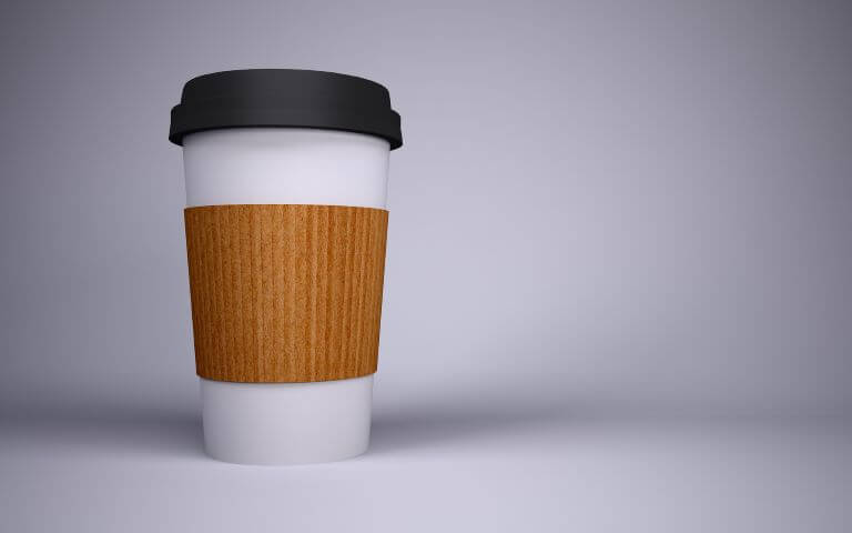 A white paper to go coffee cup with a corrugated wrap and black lid for an article about convenient products and services