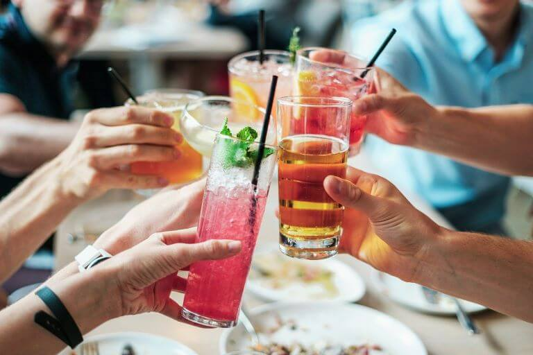 A group of people toasting with non-alcoholic beverages for an article about the sober curious trend