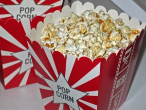 A close up of two red and white cartons of movie popcorn for an ingredient article about new popcorn flavors in beverages and desserts
