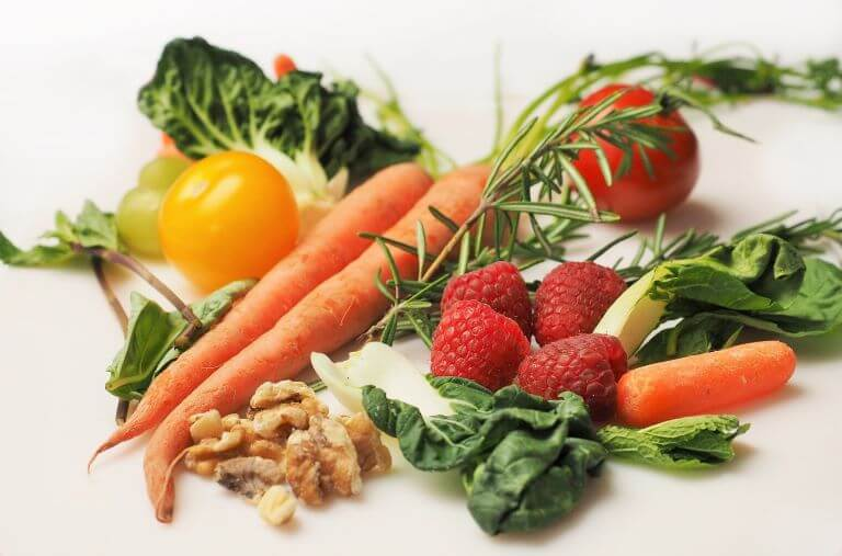 A pile of raw fruits and vegetables including carrots, raspberries, yellow tomato, rosemary, leafy greens and walnuts for a raw food article