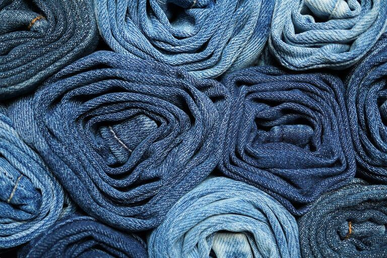 Rolled denim jeans as an example of scented clothes for a fragrance article about multi-sensory scented products