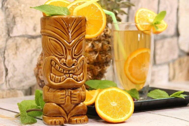 A close up of a Tiki cocktail with orange slices and mint for a lifestyle trend article on Tiki themed products and services