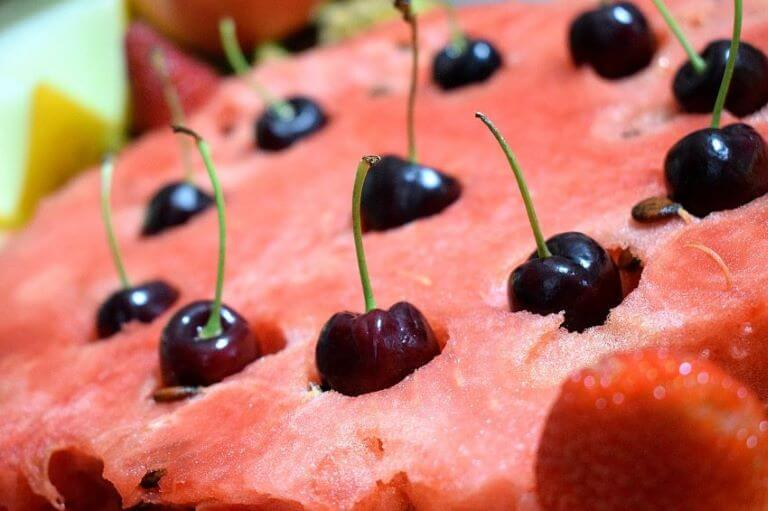 Close up of a watermelon with cherries stuck on top for an ingredient article about watermelon and cherry fragrances and flavors