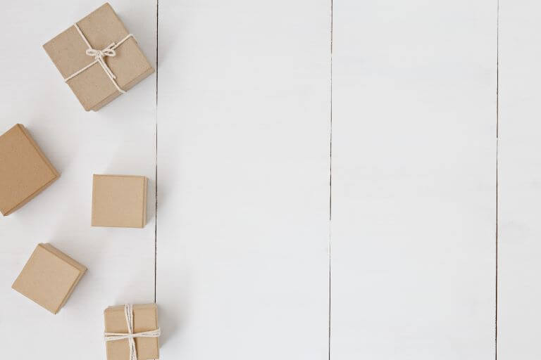 White wooden background with five small brown boxes for a design and packaging article about innovative cosmetic and personal care applicators and delivery systems