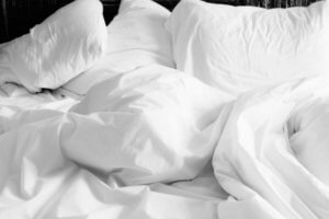 A unmade bed with white sheets and pillows for a lifestyle article about new sleep products