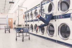 A woman inside a washing machine at a laundromat for an article about how laundry became luxurious