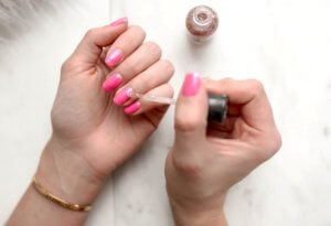A woman giving herself a manicure with pink glittery nail polish for an article about natural and nontoxic nail polish