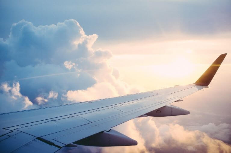 Close up of airplane wing in sunshine and clouds for article about hospitality and travel