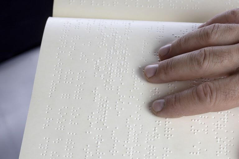 Hand reading braille to depict inclusive consumer goods packaging design