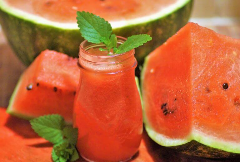 Image of watermelons and fresh watermelon juice to represent seasonal watermelon flavors in non-alcoholic and alcoholic beverages