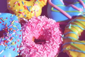 Close up of colorful pink, turquoise and yellow donuts with sprinkles for a trend article on donut flavors