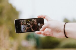 Selfie on mobile phone that shows group of young Gen Z demographic in photo with a camera taking picture