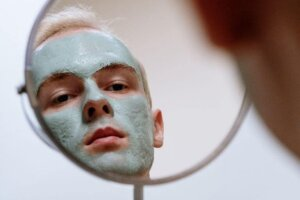 Close up of a Caucasian man with a green facial mask looking in a mirror for a trend article about men's skin care